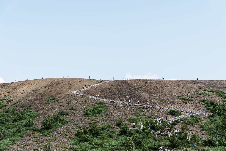 浄土平から見た火口を目指す登山者